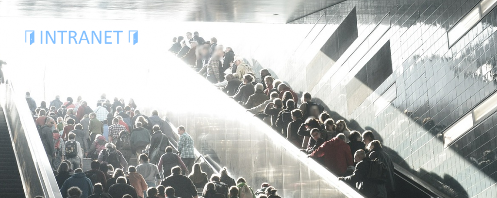 Eine Menschenmenge bewegt sich in Richtung eines Intranet-Schildes; eine Hälfte der Menschenmenge benutzt die Treppe, die andere Hälfte benutzt eine Rolltreppe.