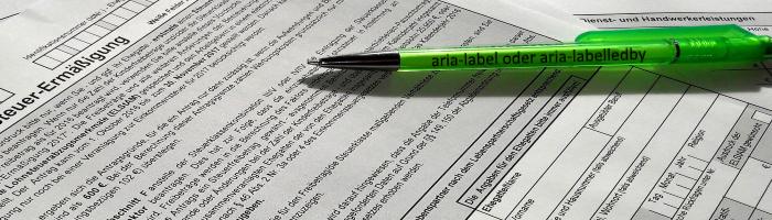 Ein Stift liegt auf einem Formular, der Stift ist mit 'aria-label oder aria-labelledby' bedruckt.