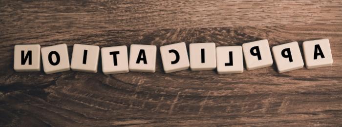 Das Wort Application gelegt mit Scrabble-Steinen in Spiegelschrift